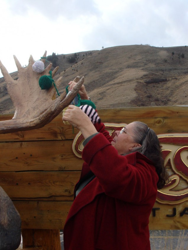 woman embellishing moose sculpture