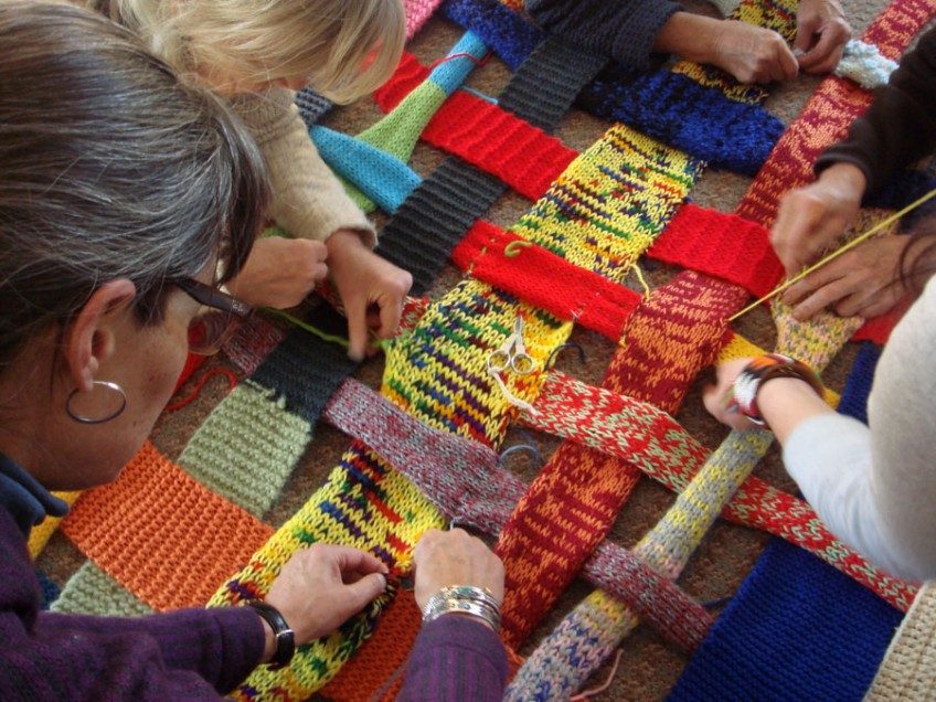 people weaving knitted strips